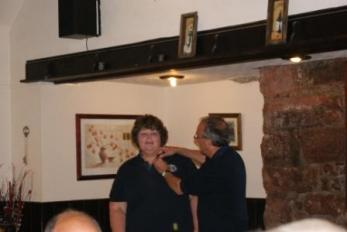 Lion President Twiggy badges up our latest member Karina Wells