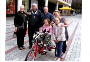 the Dunn family being presented with the special tricycle donated to by Exeter West Club, by Lion Preident Mike and Lion Caril